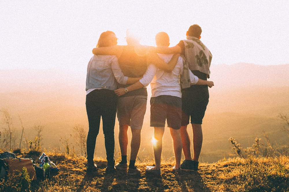 A group of friends together on top of a mountain