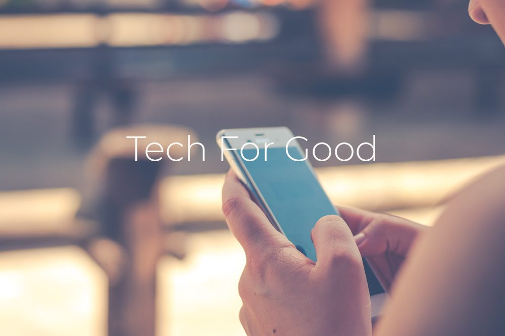 Image of a person holding a mobile phone with the words 'Tech For Good' written
