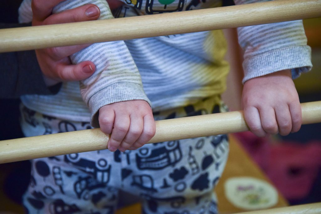 A toddler holding on to a wooden bar