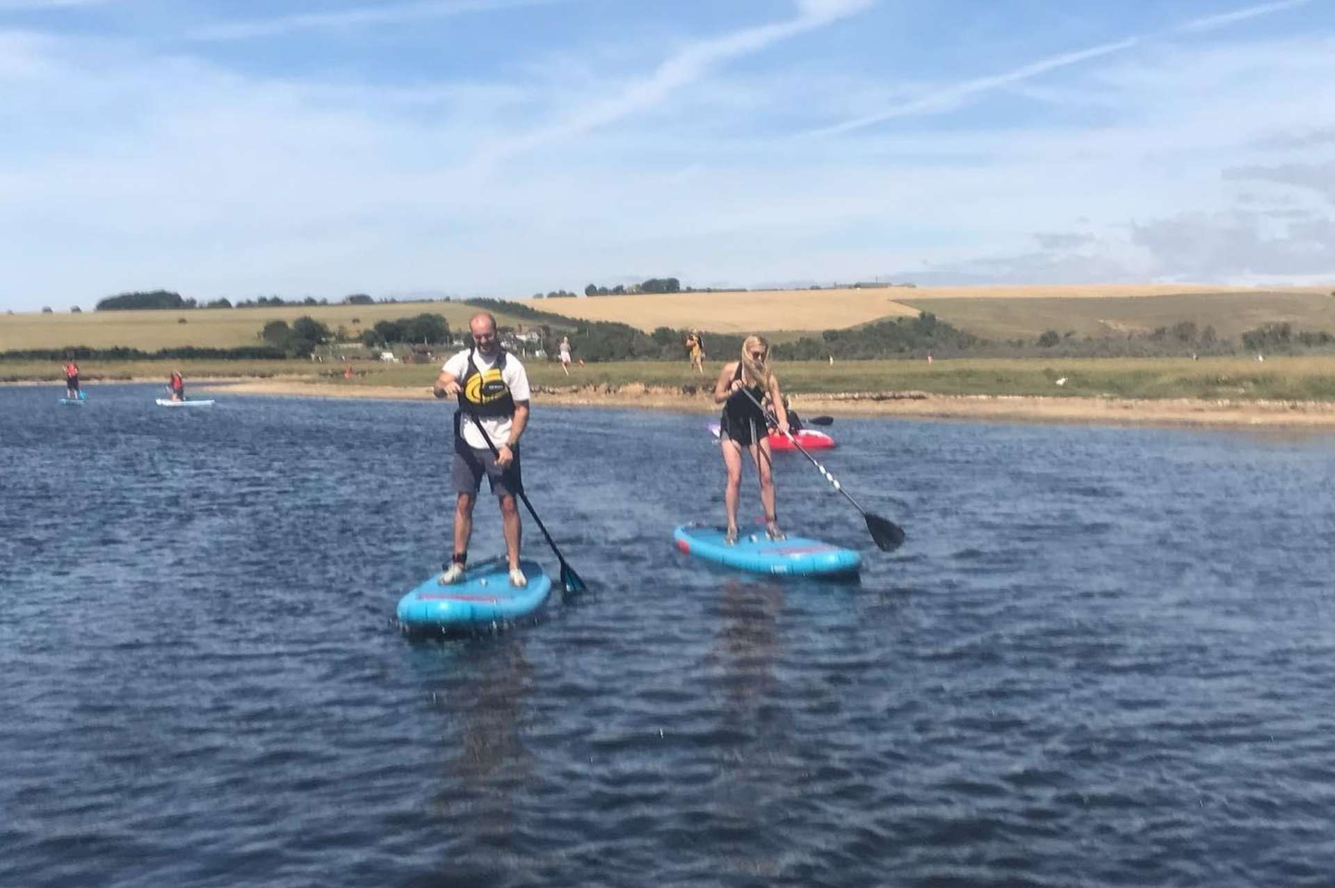 two people paddle boarding on cuckmere haven in sussex